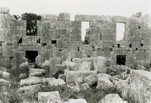 Black and white photograph of a ruined building. Large rectangular stones stacked as a wall with windows and doors.