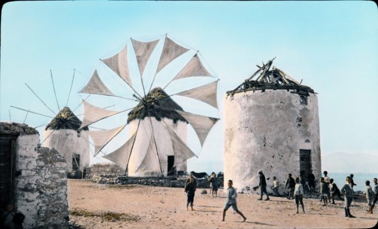 old hand colored photograph of children playing in front of windmills with triangular sails