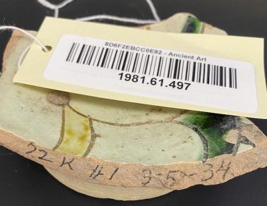Piece of pottery, cream, green and yellow glazed, with handwritten numbers on the edge