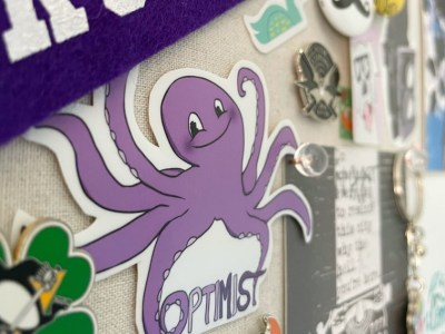 a colorful bulletin board displaying stickers, photos, artwork, and keychains