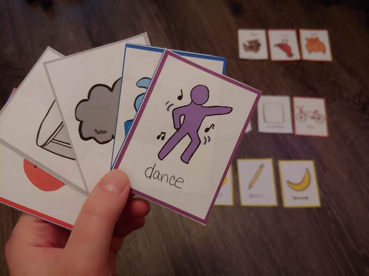 A hand holding illustrated cards with more cards on laid out in the background