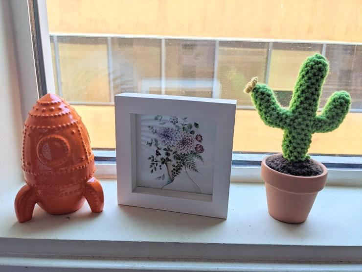 Knickknacks and a small painting sitting on windowsill