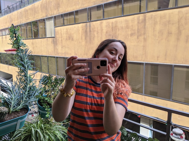 A woman peeking out from behind a smartphone as she takes a photo
