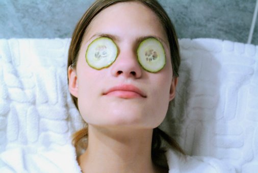 High angle view of a mid adult woman with cucumber slices on her eyes