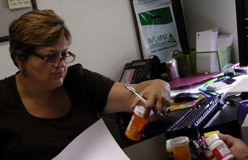 staff member inspects medicine