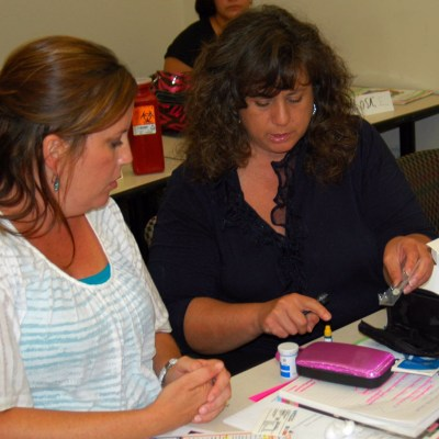 Health educator demonstrates glucose testing.