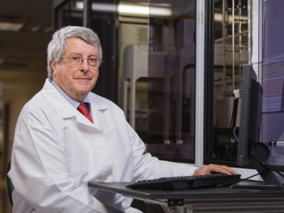 Dr. Peter Davies sitting at robotic workstation of the high-throughput equipment