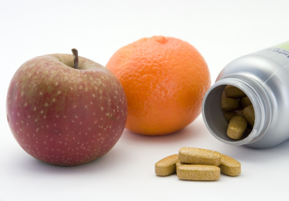 An apple and an orange next to vitamin tablets