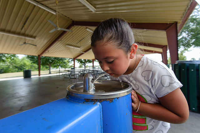 Young girl drinking from a water fountain.