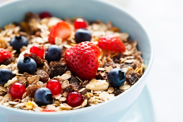 A bowl of granola cereal, with berries on top