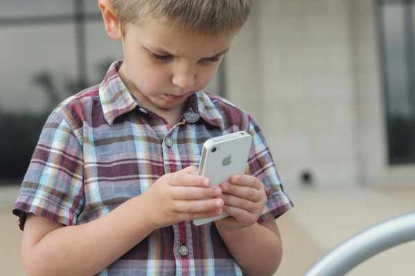 Little boy looking at phone.