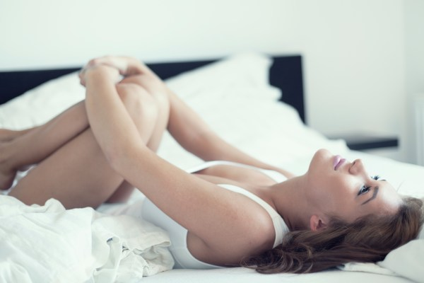 Woman lying on bed hugging her knees to her chest.