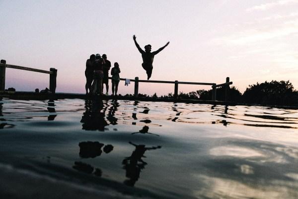 People swimming near a dock