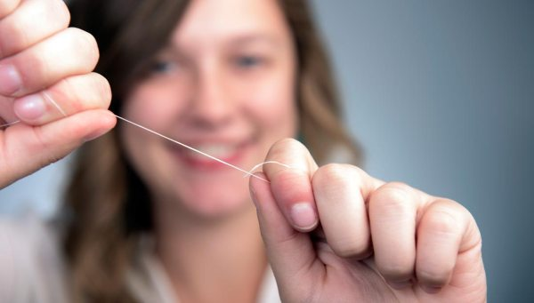 Woman holding up floss.
