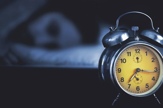 alarm clock next to person with sleeping disorders