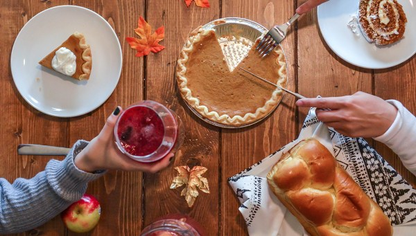 A table with pumpkin pie, bread, fall leaves and hands reaching for the food.