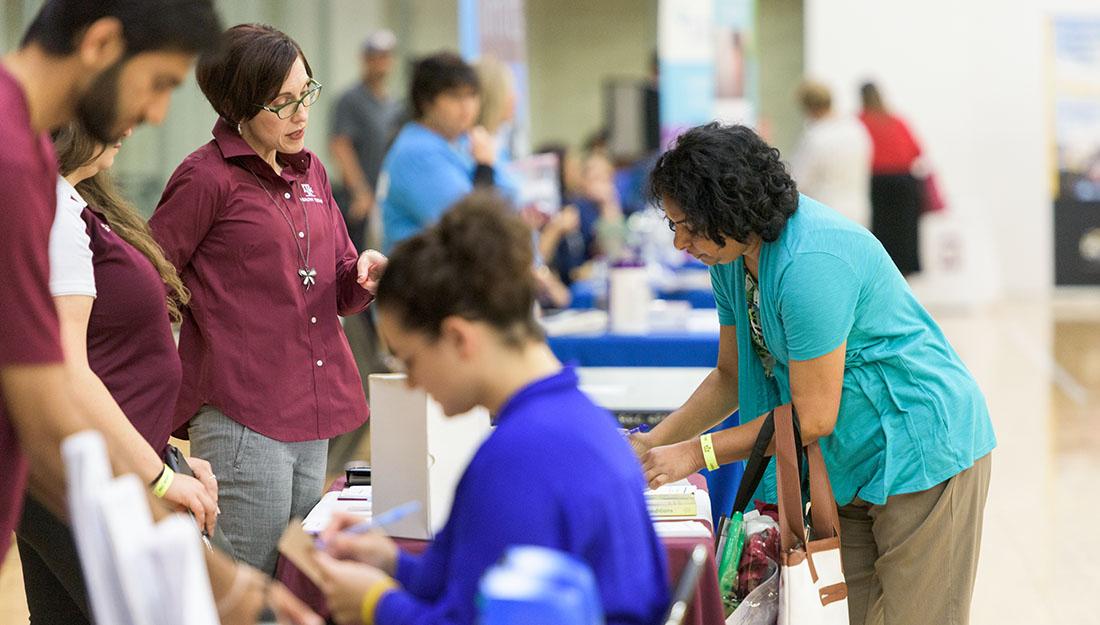 Health educators talk with participants at a community health event.