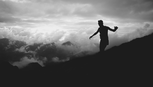 Silhouette of a person walking on the top of a mountain