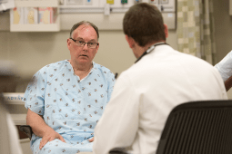 Man in a hospital gown speaking with a physician in a white coat about his pain levels