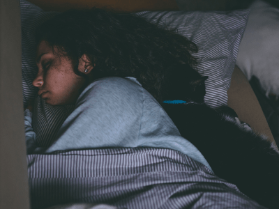 Woman asleep in a bed with a cat. Nighttime Asthma