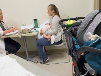 Overactive bladder-A female health care provider is sitting across the table from a new mother