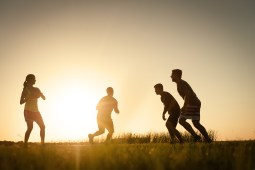 Eastern equine encephalitis_EEE_Four figures are playing football outside at sun set