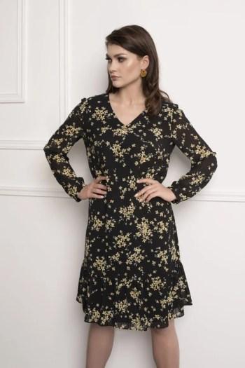 Modelka w sukienkce Vito Vergelis. Czarna sukienka z długim rękawem w żółte kwiatki z falbanami.