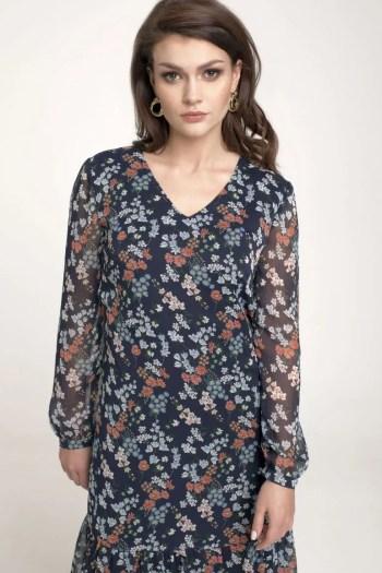 Modelka w sukience Vito Vergelis. Granatowa sukienka z długim rękawem i falbanką w kolorowe kwiatki z kreszowanego szyfonu.