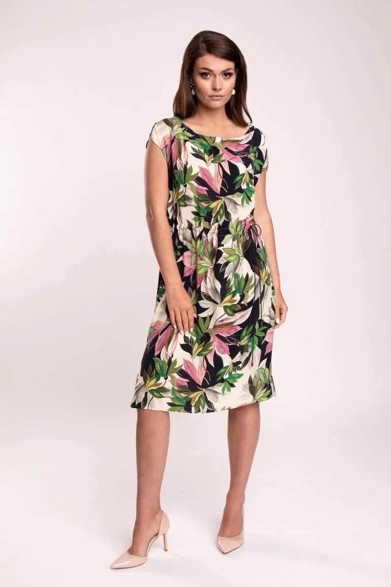 Modelka w wizytowej sukience Vito Vergelis. Ściągana sukienka z wiskozy cupro w nadruk liści i kwiatów.