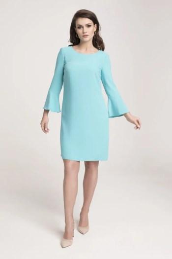 Modelka w sukience Vito Vergelis. Turkusowa sukienka z długim rękawem wykończonym roszerzanymi mankietami i lekko rozkloszowanym dołem.