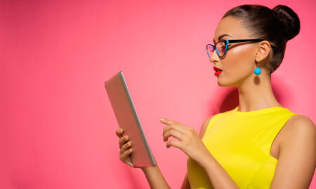 AdobeStock_woman_pink_wall_yellow_dress_tablet_social_media, 8 Social Media Marketing Secrets That Can Save You Time