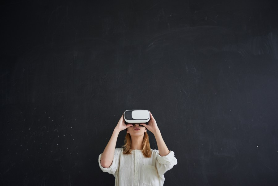 The girl in white stands on a black background in the virtual reality helmet