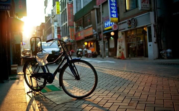 city-street-houses-shops-signs-vetrino-roads-sidewalks-bike-morning-sun-rays