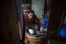 Zhu Chaorong roasts newly harvested tea leaves in an pan at his home where his family have a plantation. By Roman Pilipey.