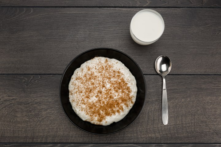 A bowl of rice porridge with a glass of milk.