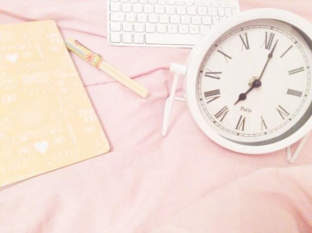 Op bed uitgestald: schrijfwaar en een klok.