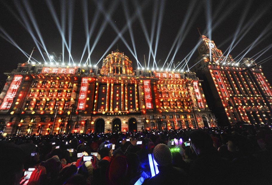 Visitors take pictures and videos during a light show as part of a New Year countdown celebration at the financial square on the Bund in Shanghai, on December 31, 2012.