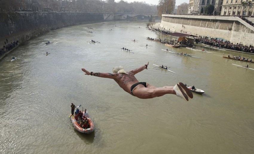 Maurizio Palmulli of Italy dives into the Tiber River from the Cavour bridge, as part of traditional New Year celebration on January 1, 2013. Four men dived the muddy waters of the Tiber from the Cavour bridge, continuing an annual tradition which dates back to 1946.