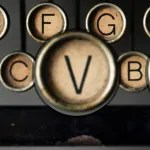 The letter 'V' from an old fashioned typewriter, enlarged compared with the surrounding letters 'C', 'F', 'G' and 'B'.