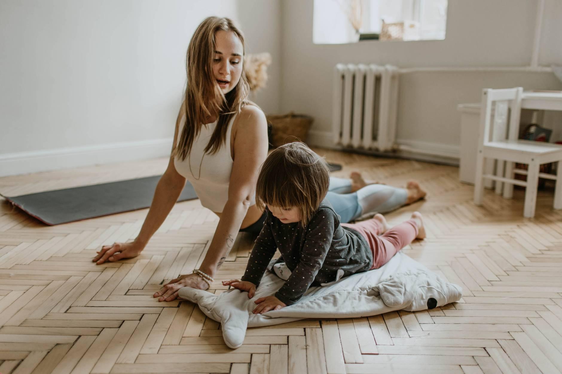 Mujer haciendo estiramientos con su hija