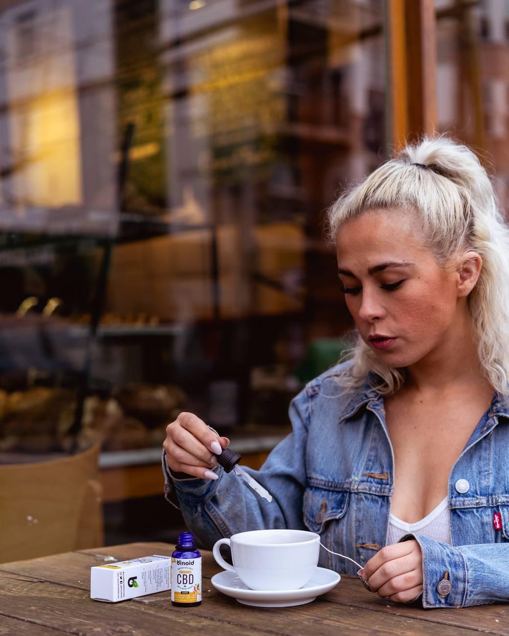 woman in blue denim jacket holding dropper