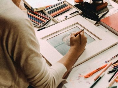 focused professional artist drawing at table