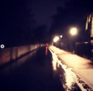 Reflet de nuit d'une personne avec un manteau rouge sur un vélo, sur une piste cyclable mouillée par la pluie et éclairée par des lampadaires.