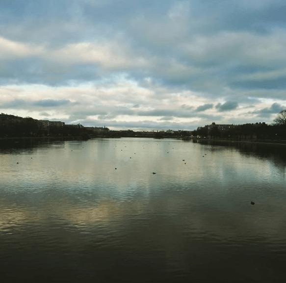 Vue sur l'un des lacs de Copenhague depuis un pont. Les nuages se reflètent de façon floue dans l'eau.