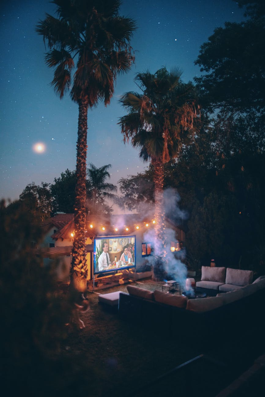 palm trees near projection screen during nighttime
