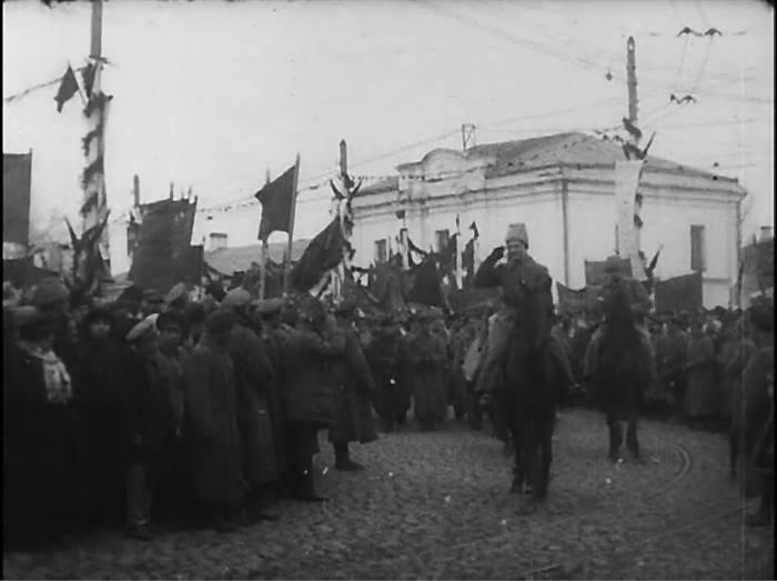 Парад 7 ноября 1918. Колонна поворачивает с площади Свободы на Замковую улиц. Кадр из кинохроники 1918 года.