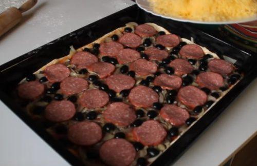 Pizza casera con salami, champiñones y aceitunas