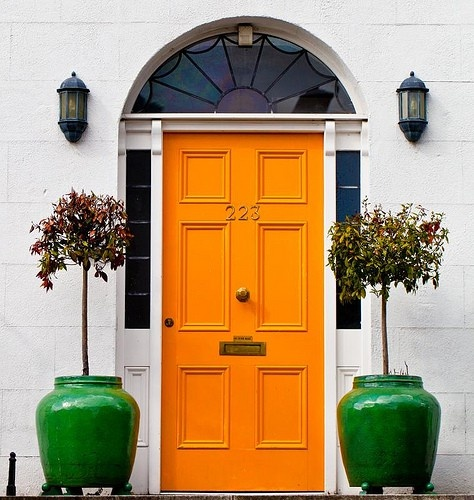 Orange front door - via House and Home
