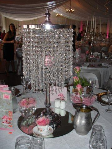 Die tafels was treffend en stylvol met wit en pienk kerse in silwer- en kristalkandelare, verskillende vorms glas vase en outydse koppies met pienk rose  versier.