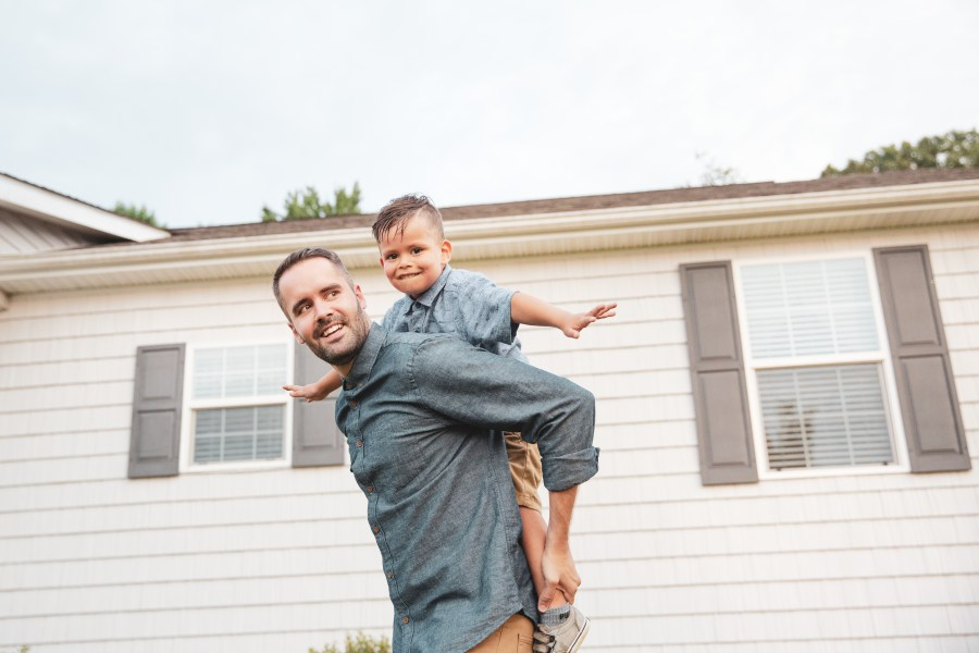 Father and child playing in front of a manufactured home.